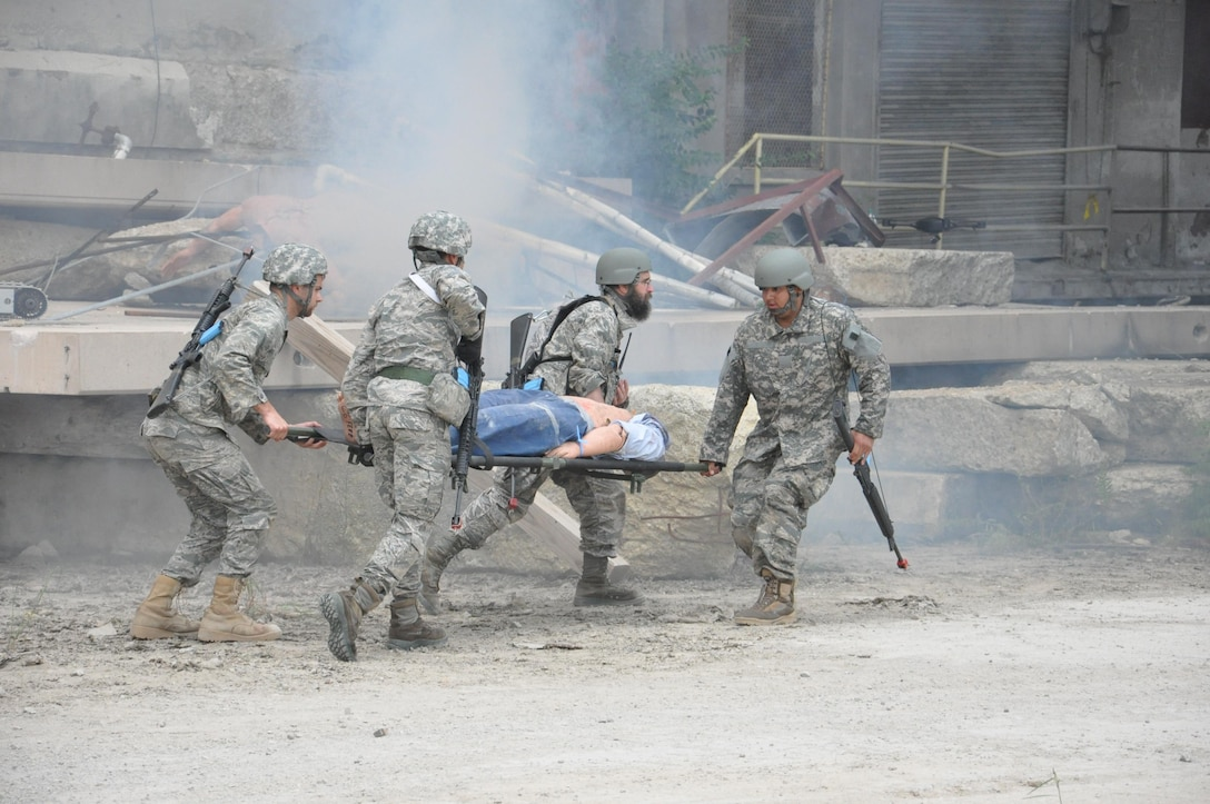 Air Force Research Laboratory Tech Warrior 2016 participants transport a casualty during a simulated battlefield scenario. The immersive experience is designed to give scientists and engineers insight into the battlefield environment in order to help in their design and function, of products and services, for the warfighter. (U.S. Air Force photo / Bill Hancock)