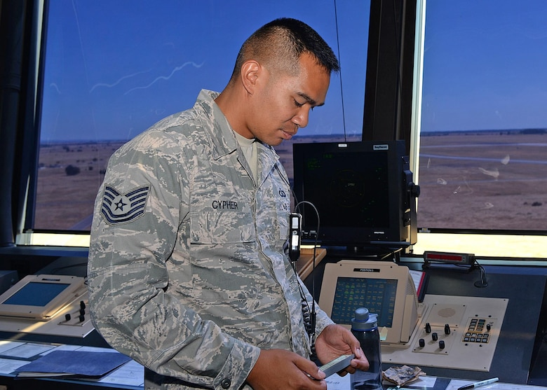 Tech. Sgt. Steven Cypher, 9th Operations Support Squadron NCO in charge of standards and evaluations, relays ground information to a pilot Aug. 31, 2016, at Beale Air Force Base, California. The information relayed ensures the pilot will be able to land safely. (U.S Air Force photo by Airman Tristan D. Viglianco)