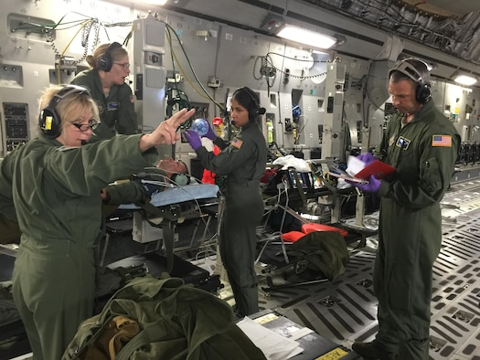 Lt. Col. Lorie O'Daniel, 446th Aeromedical Evacuation Squadron deputy officer-in-charge of commander support services and instructor flight nurse directs medical response to a simulated cardiac arrest situation. Col. Sean Pierce, 446th Operations Group commander, served as a simulated patient during one of the training sessions during the flight. (Photo by Maj. Brooke Cortez)