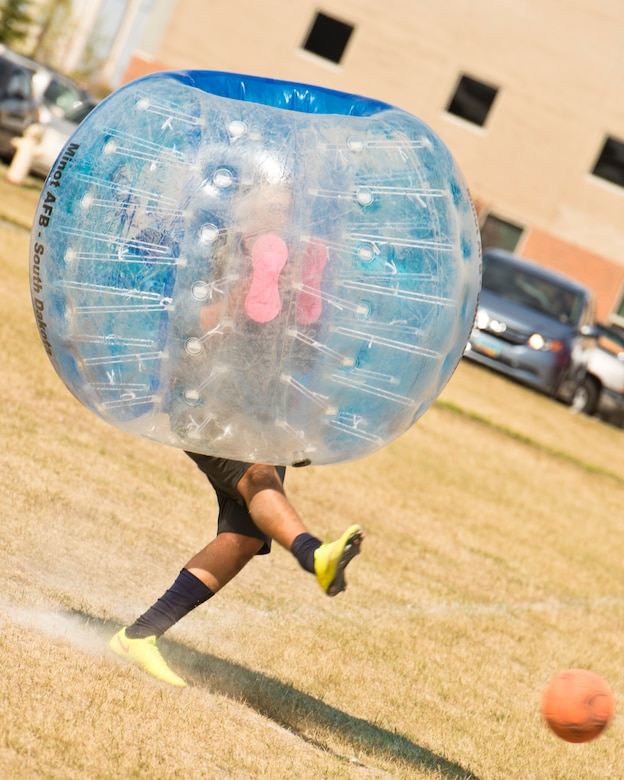 A Team Minot Airman kicks a soccer ball while playing knockerball during the Summer Games at Minot Air Force Base, N.D., Aug. 30, 2016. In knockerball, a variation of soccer, participants wear large inflatable bubbles around their upper body that allows them to bounce off other players, and makes falling down a bit more fun. (U.S. Air Force photo/Airman 1st Class J.T. Armstrong)