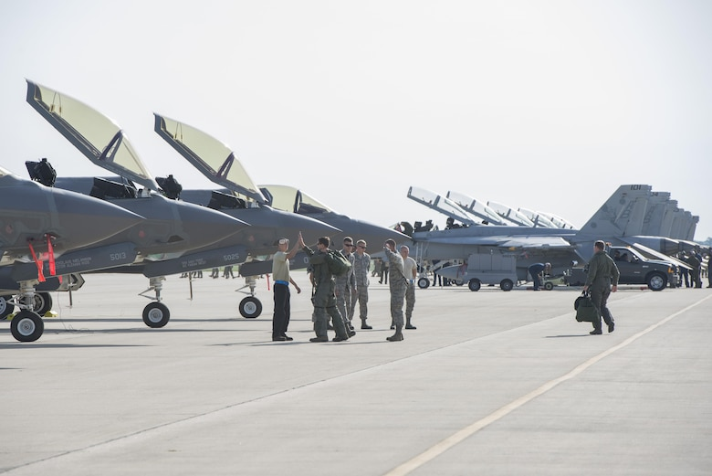 33rd Aircraft Maintenance Squadron crew chiefs greet 33rd Fighter Wing pilots as they step to their jets during exercise Northern Lightning Aug. 26, 2016, at Volk Field, Wis. Northern Lightning is a joint total force exercise between the Air National Guard, Air Force and Navy conducting offensive counter air, suppression and destruction of enemy air defense and close air support. (U.S. Air Force photo by Senior Airman Stormy Archer)