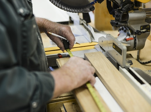Joe, the 49th Force Support Squadron Wood Shop supervisor, measures a board of redwood at Holloman Air Force Base, N.M. 23 Aug. 2016. Airmen and civilians can utilize the shop's premium woodworking equipment to work on personal projects. (Last names are being withheld due to operational requirements. U.S. Air Force photo by Airman Alexis P. Docherty)
