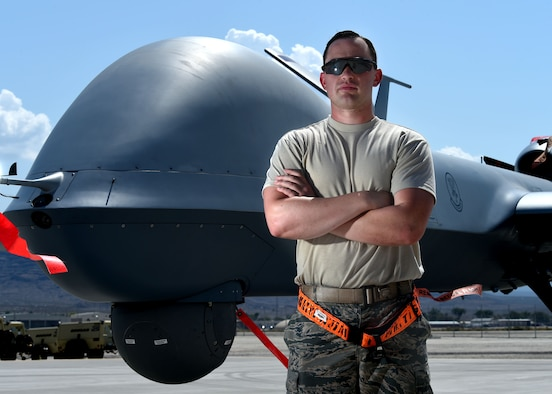 A crew chief assigned to the 432nd Aircraft Maintenance Squadron Tiger Aircraft Maintenance Unit poses for a photo in front of an MQ-9 Reaper Aug. 24, 2016, at Creech Air Force Base, Nevada.  The first MQ-9 launch from Tiger Aircraft Maintenance Unit signals the start of the transition to an all MQ-9 force. (U.S. Air force photo by Airman 1st Class James Thompson)