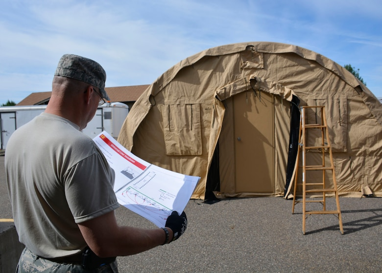 120th Sustainment Services Flight Management and Program Assistant Master Sgt. Troy Anderson reviews instructions while members of the 120th SSF construct an Alaska Small Shelter System during the guard drill at the 120th Airlift Wing in Great Falls, Mont. Aug. 13, 2016. (U.S. Air National Guard photo by Senior Master Sgt. Eric Peterson)
