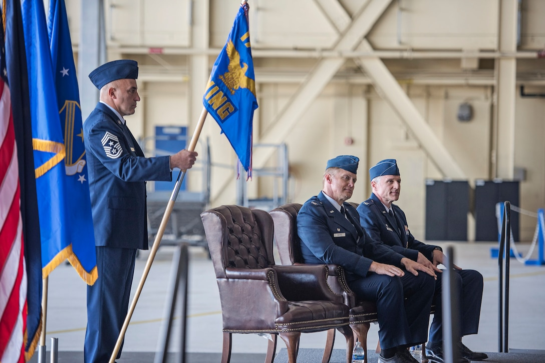Command Chief Master Sgt. David Garganta, senior enlisted leader of the 176th Wing, Alaska Air National Guard, holds the unit guidon while Col. Blake Gettys and Col. Steven deMilliano sit during a change-of-command ceremony on Joint Base Elmendorf-Richardson, Alaska, July 12. Gettys, who served as the 176th Wing's commander since 2014, relinquished control of the wing to deMilliano during the ceremony. (U.S. Air National Guard photo by Staff Sgt. Edward Eagerton/released)