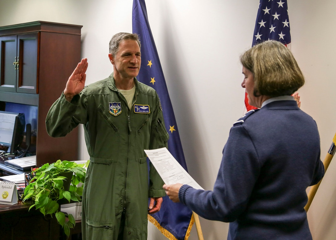 Brig. Gen. Karen Mansfield, Alaska Air National Guard commander, administers the oath of office to Col. Steven deMilliano, 176th Wing incoming commander, during a ceremony at the National Guard Armory on Joint Base Elmendorf-Richardson, July 11, 2016. (U.S. Army photo by Staff Sgt. Balinda O'Neal Dresel)