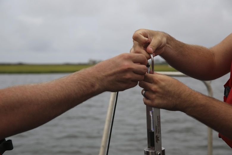 U.S. Marines with Battlefield Surveillance Company, 2nd Intelligence Battalion, tie a cord around a digibar before letting it underwater to collect information such as sound velocity off the coast of Oak Island, N.C., Aug. 31, 2016. The Marines teamed up with U.S. Coast Guardsmen at USCG Station Oak Island, N.C., to create a topographical layout of waterways that were previously unidentifiable. The new maps will correct navigation discrepancies such as off-station buoys or extinguished lights. (U.S. Marine Corps photo by Cpl. Kaitlyn V. Klein)