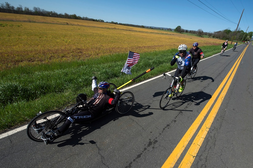 Medically retired Navy Petty Officer 1st Class Jerry W. Padgett II, front, raises his arms during the Face of America bike route in Gettysburg, Pa., April 24, 2016. More than 150 disabled veteran cyclists were paired among 600 able-bodied cyclists to ride 110 miles from Arlington, Va. to Gettysburg, Pa., over two days in honor of veterans and military members. DoD photo by EJ Hersom