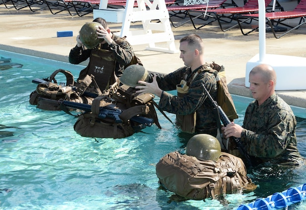 Marines prepare to use their packs as a floating device during their annual swim qualification at the Base Pool aboard Marine Corps Logistics Base Albany, Aug 24.