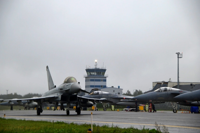 A Royal Air Force Typhoon passes a fleet of F-15C Eagles at Ämari Air Base, Estonia, Aug. 17, 2016. Five countries, including the U.S., U.K., Estonia, Sweden and Finland, participated in a flying training deployment, which allowed for various aircraft and Airmen to test their capabilities against each other in a realistic training environment. (U.S. Air Force photo by Senior Airman Erin Trower/Released)