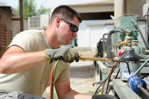 Senior Airman Kyle Cvoliga, 386th Expeditionary Civil Engineer Squadron heating, ventilation, and air conditioning technician, uses a blowtorch to fix a leak on an A/C unit Sep. 2, 2016, at an undisclosed location in Southwest Asia. The 386 ECES HVAC shop is responsible for fixing and maintaining over 725 A/C units across the base. (U.S. Air Force photo/Senior Airman Zachary Kee)