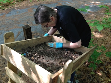Archeologist Kate Atwood begins the process of sorting through dirt and rocks to look for artifacts.