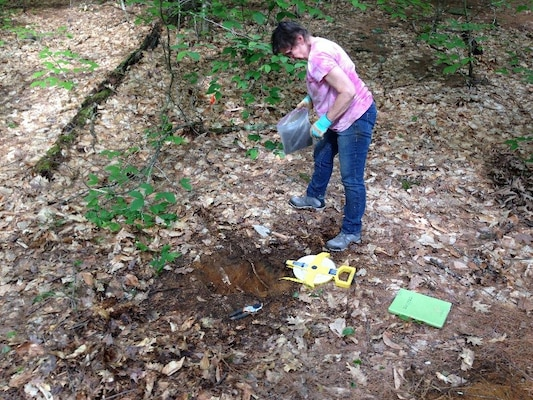 Kate Atwood removes material from a test pit for analysis.