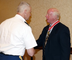 Col. Barron shakes Bill Scully's hand after presenting him with the Bronze De Fleury Medal during his retirement party at the Escadrille Restaraunt in Burlington, Massachusetts on August 11, 2016.