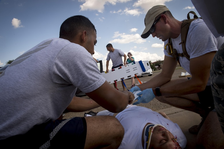 Emergency medical technicians assigned to Malmstrom Air Force Base, Mont., treat a simulated severe care accident victim while teammates try to extract a victim from the car during the 2016 EMT Rodeo Aug. 26, 2016 at Cannon Air Force Base, N.M. Cannon's EMT Rodeo tests the skills of medical professionals from across the Air Force through a series of innovative, high-pressure scenarios. (U.S. Air Force photo by Tech. Sgt. Manuel J. Martinez)