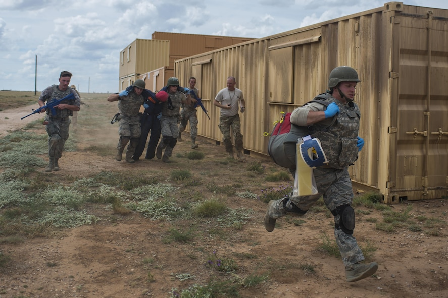 Emergency medical technicians, assigned to the 92nd Medical Group at Fairchild Air Force Base, Wash., carry a simulated patient for the Commando Challenge during the 2016 EMT Rodeo at Melrose Air Force Range, N.M., Aug. 25, 2016. Cannon's EMT Rodeo tests the skills of medical professionals from across the Air Force through a series of innovative, high-pressure scenarios. (U.S. Air Force photo by Senior Airman Luke Kitterman/Released)