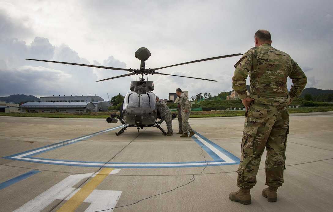 U.S. Army Col. Michael Harvey, I Corps executive officer to the commanding general, watches an OH-58D Kiowa Warrior crew prepare for takeoff from an airfield in Yongin, South Korea, Aug. 29, 2016. The helicopter belonged to the 1st Squadron, 17th Cavalry Regiment, the last squadron of OH-58's. Once their deployment is over the Army will retire all OH-58's from its fleet. Harvey logged more than 1,900 hours flying the aircraft during his Army career. (U.S. Army photo by Staff Sgt. Ken Scar)