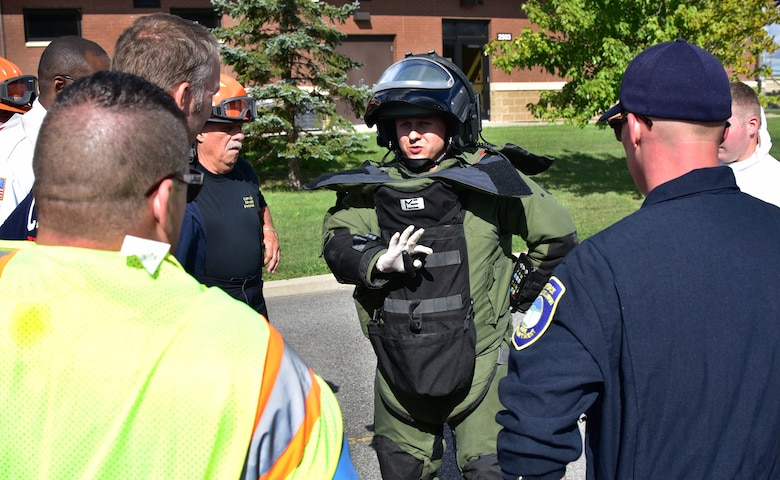 Tech. Sgt. Aaron Clark, EOD team leader, 914th Airlift Wing Civil Engineer Squadron, instructs various base first responder personnel on the removal of an EOD bomb suit at an exercise on Thursday, September 1, 2016. The exercise showcased interoperability of base and local first responder units in a simulated bomb attack. (U.S. Air Force photo by Staff Sgt. Richard Mekkri/released)