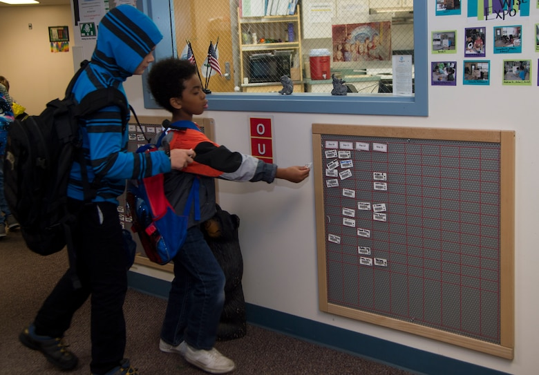 Joshua Gaspard (left to right), 9, and Devin Hogan, 7, sign their name on the board on their way to school from Ketchikan School Age Centers at Joint Base Elmendorf-Richardson, Alaska, Sept. 6, 2016. Ketchikan School Age Center offers a wide range of activities including computer lab, arts programs and field trips. (U.S. Air Force photo by Staff Sgt. Sheila deVera)