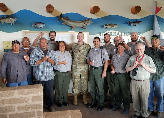 COCHITI LAKE, N.M. -- District employees at Cochiti Lake show their commander's coins, Aug. 19, 2016. District Commander Lt. Col. Booth presented the coins to recognize the employees' role in the successful outcome of the two rescues.
