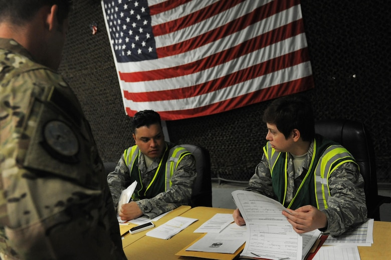 U.S. Air Force Airman 1st Class Anthony Licea, 19th Force Support Squadron decorations technician, and U.S. Air Force Airman 1st Class Xochitl Medina, 19th Force Support Squadron relocations technician, review paperwork during a personnel deployment function line Sept. 1, 2016, at Little Rock Air Force Base, Ark. During a PDF line, Airmen have their records reviewed prior to deploying. (U.S. Air Force photo by Senior Airman Mercedes Taylor)