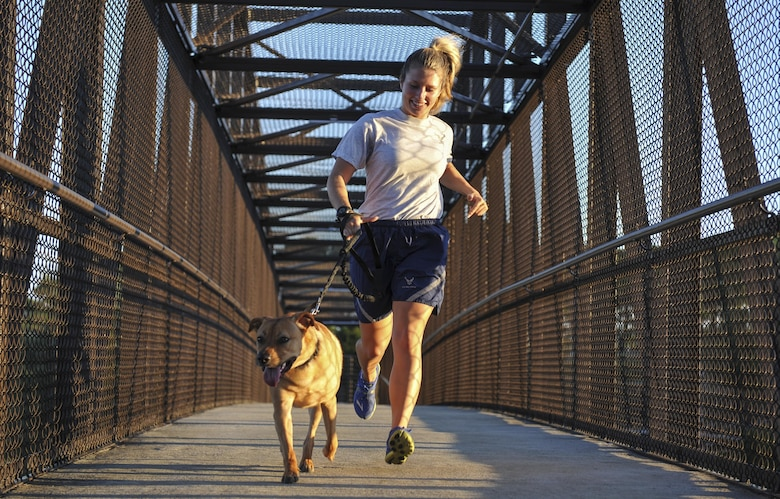 Senior Airman Rebecca Chamberlain, a paralegal with the 1st Special Operations Wing Legal Office, runs with her dog, Cecil, at Hurlburt Field, Fla., Aug. 30, 2016. Chamberlain often runs with Cecil as she prepares for the 20th Annual Air Force Marathon scheduled to take place Sept. 17, at Wright-Patterson Air Force Base. (U.S. Air Force photo by Airman 1st Class Joseph Pick)