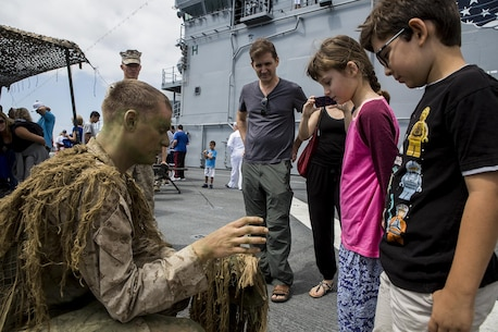 U.S. Marine Cpl. Cory Mersino, a rifleman with Scout Sniper Platoon, 3rd Battalion, 5th Marine Regiment, teaches children about his ghillie suit, during a demonstration as part of Los Angeles Fleet Week in San Pedro, Calif., Sept. 4, 2016. L.A. Fleet Week is an event designed to showcase the capabilities of the Navy-Marine Corps team to L.A. residents, and an opportunity for members of the sea services to meet and thank the community for its support. (U.S. Marine Corps photo by Sgt. Rick Hurtado)