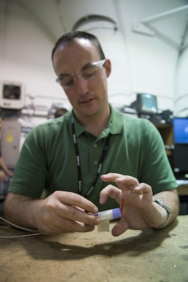 Kane Ivory, an electrical engineer from Melbourne, Australia, adds thermal couplers and a heating cartridge to a lithium ion cell to run a thermal abuse test on the cell in West Bethesda, Md., Aug. 29, 2016. Ivory is temporarily assigned to Naval Surface Warfare Center, Carderock Division under the Department of Defense's Engineer and Scientist Exchange Program. (U.S. Navy photo by Dustin Q. Diaz/Released)