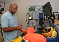 Harold R. Washington, 9th Physiological Support Squadron suit maintenance technician, inflates the life preserve device of a full pressure suit Aug. 31, 2016, at Beale Air Force Base, California. In the event of a crash the life preserve device is designed to inflate upon contact with water. (U.S. Air Force photo/Airman Tristan D. Viglianco)