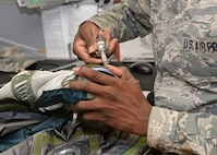 Senior Airman Simon Adeniji, 9th Physiological Support Squadron full pressure suit technician, tightens bolts during an inspection of a full pressure suit Aug. 31, 2016, at Beale Air Force Base, California. Inspections of the full pressure suits occur on a regular basis to check for any problems. (U.S. Air Force photo/Airman Tristan D. Viglianco)
