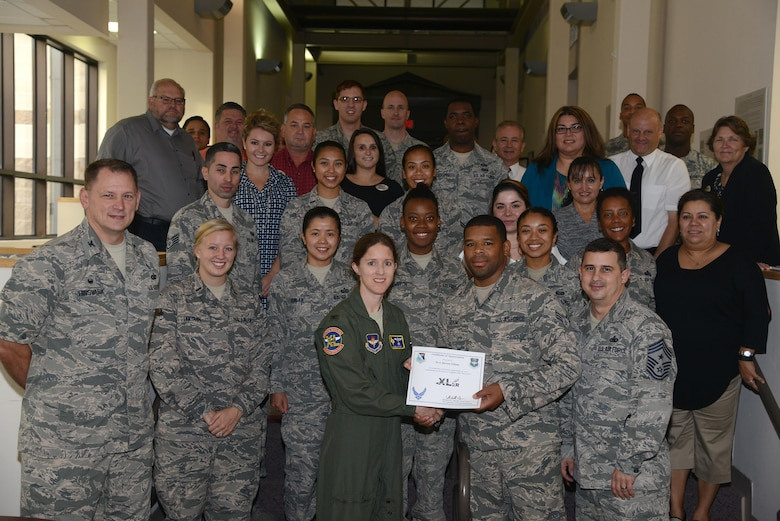 """Senior Airman Steven Odom, front center, 47th Force Support Squadron management apprentice, accepts the """"XLer of the Week"""" award from Col. Michelle Pryor, 47th Flying Training Wing vice commander, and Chief Master Sgt. George Richey, 47th FTW command chief on Laughlin Air Force Base, Texas, Aug. 31, 2016. The XLer is a weekly award chosen by wing leadership and is presented to those who consistently make outstanding contributions to their unit and Laughlin. (U.S. Air Force photo/Airman 1st Class Brandon May)"""