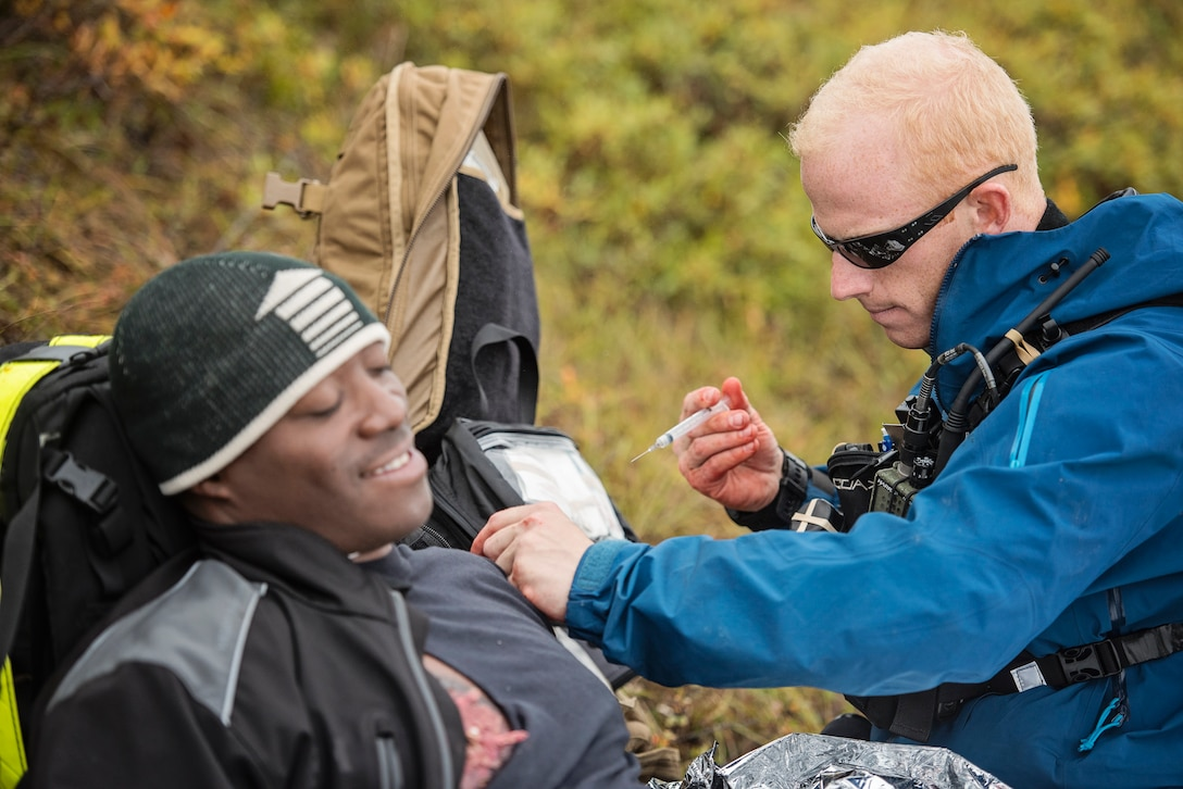 A pararescueman from the 212th Rescue Squadron, Alaska Air National Guard, treats a simulated casualty during exercise Arctic Chinook, near Kotzebue, Alaska, August 23. Arctic Chinook is a joint U.S. Coast Guard and U.S. Northern Command sponsored exercise which focuses on multinational search and rescue readiness to respond to a mass rescue operation requirement in the Arctic. (U.S. Air National Guard photo by Staff Sgt, Edward Eagerton/released)