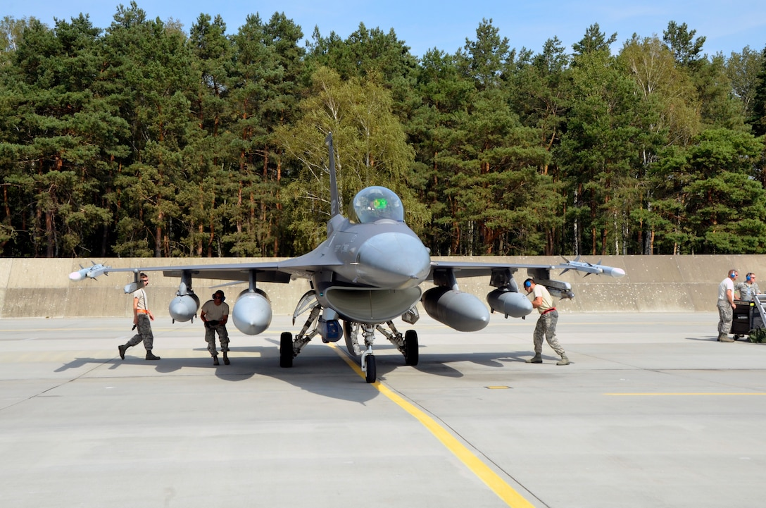 Lask Air Base, Poland -- Members of the South Dakota Air National Guard 114th Maintenance Group immediately began an initial cursory inspection of an F-16 Fighting Falcon upon arrival here Sept. 3. Additional recovery procedures are then performed after the aircraft is shut down. (U.S. Air National Guard photo by Capt. Amy Rittberger/Released)