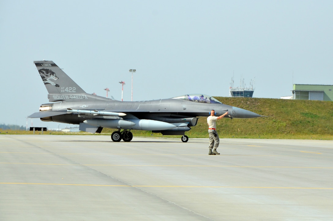 Lask Air Base, Poland - Master Sgt. Ryan Bak, South Dakota Air National Guard 114th Aircraft Maintenance Squadron crew chief, directs an F-16 Fighting Falcon to its parking spot as it arrives here Sept. 3. More than 100 members of the 114FW are deployed in support of Aviation Detachment 16-4, a bilateral training exercise between the U.S. and Polish forces. (U.S. Air National Guard photo by Capt. Amy Rittberger/Released)