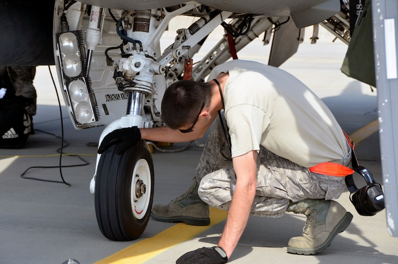 Lask Air Base, Poland -- Tech. Sgt. Scott Schmit, 114th Aircraft Maintenance Squadron crew chief, inspects a nose tire on an F-16 Fighting Falcon after arriving here Sept. 3. A thorough inspection is accomplished after each flight to ensure the jet is safe and ready to fly the next mission.  (U.S. Air National Guard photo by Capt. Amy Rittberger/Released)