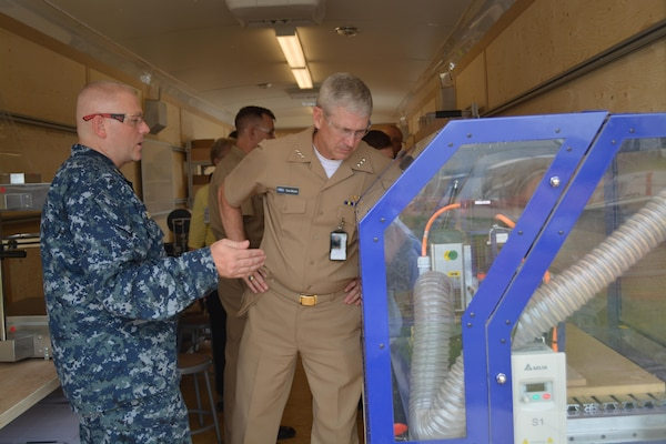 Senior Chief Machinery Repairman Sean A. Boykin explains the functionality of a 3-D Computer Numerically Controlled (CNC) Router to VADM Thomas J. Moore, Naval Sea Systems Commander inside the Fabrication Laboratory, or Fab Lab, at Southeast Regional Maintenance Center (SERMC).