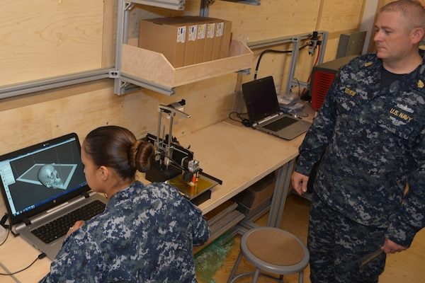 Machinery Repairman Senior Chief Shawn Boykin observes as Machinery Repairman 2nd Class Lisa Petyak as she experiments with the 3-D printing capabilities inside the new Fabrication Laboratory, or Fab Lab at SERMC. DARPA delivered the Fab Lab to SERMC earlier this month under their Manufacturing Experimentation and Outreach Two (MENTOR2) program.