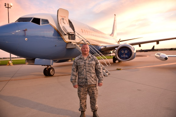 Tech. Sgt. Joseph Reinhold stands before a 932nd Airlift Wing C-40C that he helps to maintain, as the sun sets in Illinois.  He assisted with setting up the static display for the recent Belle-Scott after hours orientation event, showing off the mission and people of the Illinois Air Force Reserve unit.  (U.S. Air Force photo by Christopher Parr)