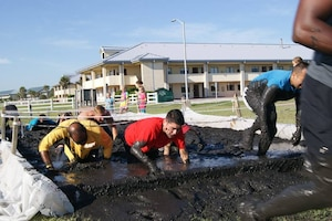 Runners race through obstacles during the Morale, Welfare and Recreation (MWR) Mayport Mud Run 2016. The event is an annual fitness challenge hosted by MWR for service members and their families to promote health and well-being.