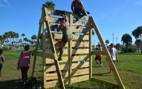 Runners climb up and over a vertical wall while participating 