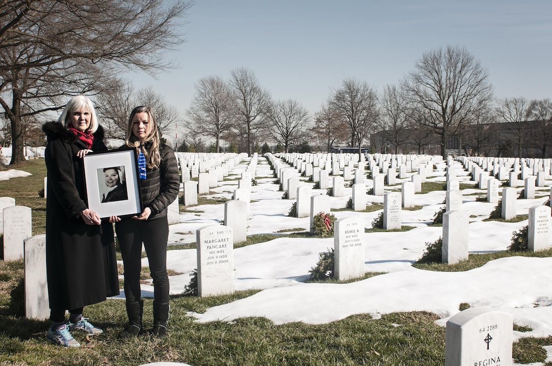 Terry Harmon and Erin Miller, daughter and granddaughter of 2nd Lt. Elaine Harmon, Women Airforce Service Pilot, hold a portrait of her in Arlington National Cemetery, Va. Jan. 31, 2016. Harmon is the first WASP to be buried in Arlington since the passing of HR-4336, a bill introduced by Rep. Martha McSally, to ensure WASPs are eligible for interment at Arlington National Cemetery. (U.S. Air Force photo/Staff Sgt. Katherine Tereyama)
