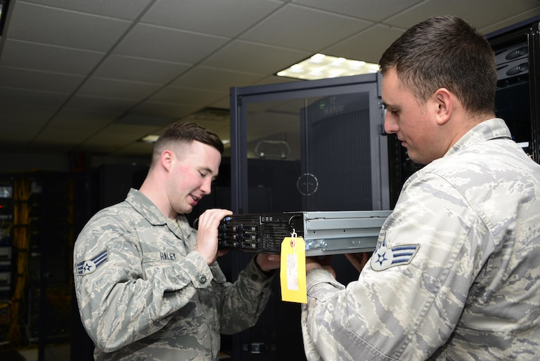 U.S. Air Force Senior Airmen Bradley Haley and Caige Kelly, 355th Communications Squadron network operations technicians, remove and replace a server at Davis-Monthan Air Force Base, Ariz., Sept. 7, 2016. The network operations team will be installing a scripting server which will be used to install software and security patches to the base network. (U.S. Air Force photo by Senior Airman Betty R. Chevalier)