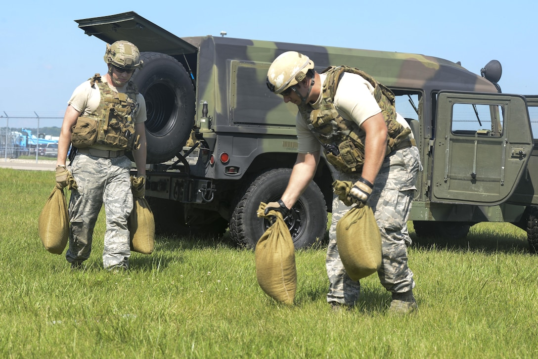 Senior Airman Tyler Squibb, and Staff Sgt. Nicholas Scheer, both explosive ordinance disposal technicians with the 788th Civil Engineer Squadron place sand bags to contain the simulated blast of an unexploded ordinance which was reported as part of an exercise, at Wright-Patterson Air Force Base, Ohio August 2, 2016. Readiness exercises are routinely held to streamline unit cohesion when responding to emergencies. (U.S. Air Force photo / Wesley Farnsworth)