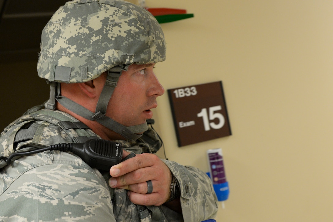 Tech. Sgt. Jeremy Parthemor, 88th Security Forces Squadron assistant flight chief, radio's in the location of two victims located during an initial sweep of the hospital clinic during active shooter exercise held inside the base hospital on Wright-Patterson Air Force Base, Ohio, August 4, 2016. The exercise was held as part of the requirement set for military installations to hold active shooter exercises twice a year. (U.S. Air Force photo / Wesley Farnsworth)
