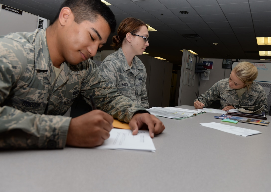 Senior  Airman Sheena Mogan (center), Military Personnel Flight, customer service apprentice, completes out-processing paperwork for her permanent change of station with Airman 1st Class Atomu Gordon and Senior Airman Ryley Harriman, both with the MPF Career Development section  at Wright-Patterson Air Force Base, Ohio, Aug. 15, 2016 . The MPF facilitates weekly in-processing and monthly newcomer orientations. Newcomers can be scheduled for both through the orderly rooms. (U.S. Air Force photo / Michelle Gigante)