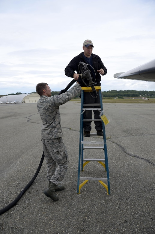 Senior Airman David K. Fink, a fuels specialist with the 445th Logistics Readiness Squadron from Wright-Patterson Air Force Base, Ohio assists a civilian maintenance personnel here as they fuel a C-12 Huron aircraft July 26, 2016 at JBER. The 445th Airman fueled many different aircraft platforms not seen at home station while on annual training. (U.S. Air Force photo/Staff Sgt. Joel McCullough)