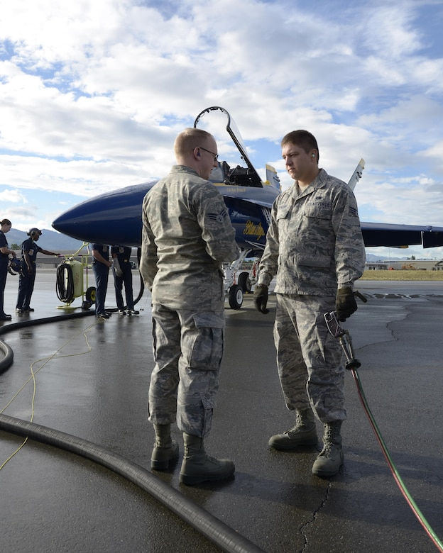 Senior Airmen Leo K. Reid and Darren M. Trenkamp, both fuels specialist from the 445th Logistics Readiness Squadron from Wright-Patterson Air Force Base, Ohio discuss procedures while refueling a Blue Angel F/A-18 Hornet here July 28, 2016. The Airmen worked alongside the Blue Angels crew to ensure the Hornets were fueled in preparation for the Artic Thunder air show being held at JBER. (U.S. Air Force photo/Staff Sgt. Joel McCullough)