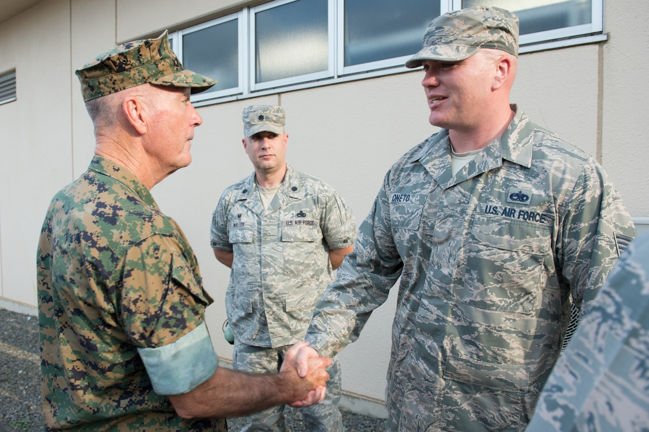 Marine Corps Gen. Joe Dunford, chairman of the Joint Chiefs of Staff, recognizes Air Force Tech Sgt. Garrett Oneto, support section noncommissioned officer in charge of the 374th Aircraft Maintenance Squadron at Yokota Air Base, Japan, for helping a fellow airman who was struggling and contemplating suicide, Sept. 7, 2016. DoD photo by Army Sgt. James K. McCann