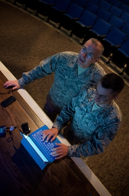 At left, Col. Jonathan Philebaum, commander of the 932nd Airlift Wing, looks up at the projected display as Staff Sgt. Justin Layton, 932nd AW communication support technician, troubleshoots getting an established connection with a portable WiFi router at the Scott Air Force Base Library Auditorium, Sep. 8, 2016.  Col. Philebaum will use an online application to interact with the audience during this commander's call Sunday of the September unit training assembly.  (U.S. Air Force photo by Christopher Parr)