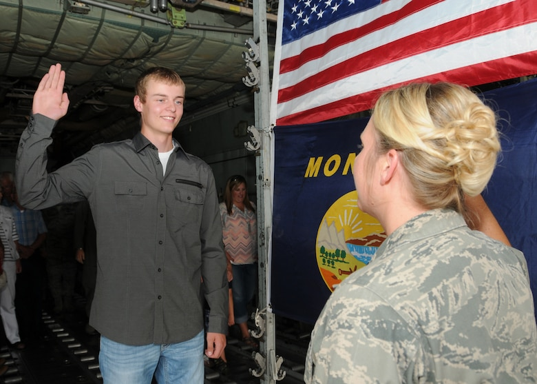 Tyler LaPierre recites the oath of enlistment during his Montana Air National Guard enlistment ceremony in the cargo hold of a C-130 Hercules transport aircraft parked at the 120th Airlift Wing in Great Falls, Mont. Aug. 31, 2016. His aunt, Capt. Jennifer LaPierre Gunter administered the oath. (U.S. Air National Guard photo by Senior Master Sgt. Eric Peterson)